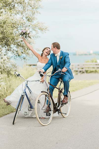Bride & Groom Sitting atop Bicycles beside waters edge