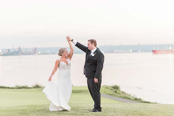 Groom Twirling his Bride Beside Water Edge