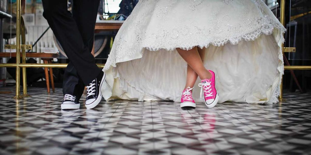 Bride Wearing Pink Sneakers under her wedding dress