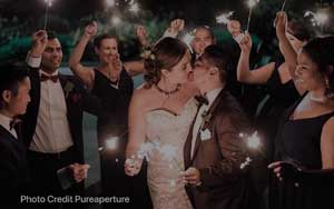 Bride & Groom Kiss while holding sparklers