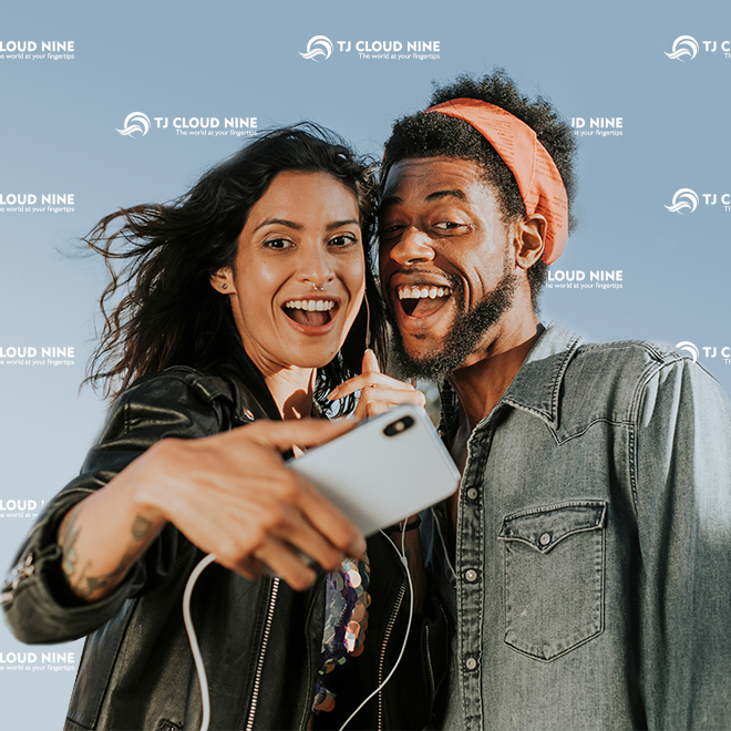 Couple taking selfie in front of custom logo media wall