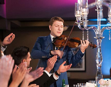 Violinist playing in front of a dinner crowd