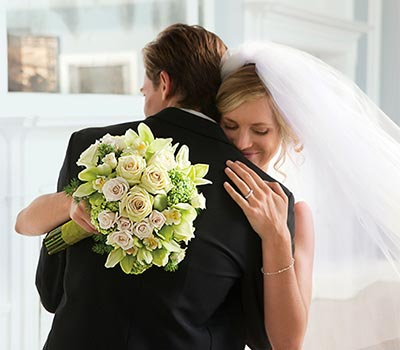 Bride hugging groom holding bouquet against his back