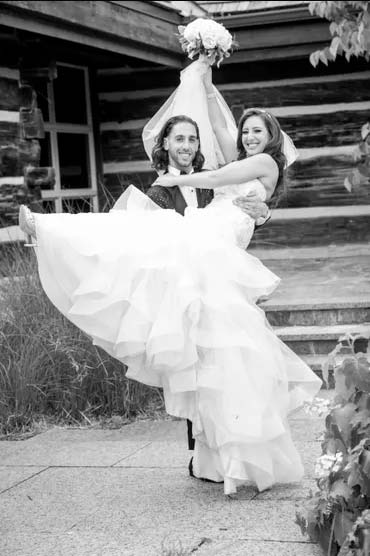 Black & White photo of Groom carrying his bride